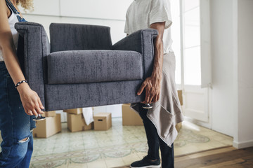 Couple carrying armchair while standing at new house