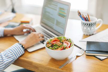 Cropped image of businesswoman blogging through laptop computer by salad bowl on wooden table at home office