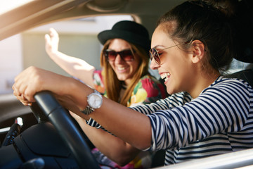 Two smiling young friends driving on a road trip together Wall mural