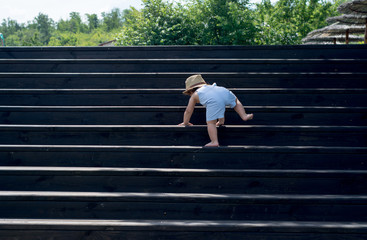 The one-year child climbs up the stairs. Cute baby boy in hat plays on the stairs. The concept of happy childhood. Nature, outdoors, summer Wall mural