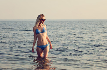 Happy, smiling woman, perfect body, wearing bikini standing on the beach. Summer holidays and vacation concept