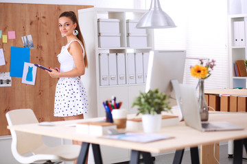 Young woman working in office, standing at desk