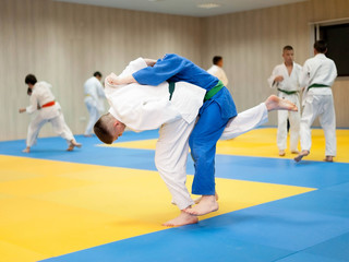Two unrecognizable judokas fighting. Judoka in white judogi throwing attacking opponent with uchimata
