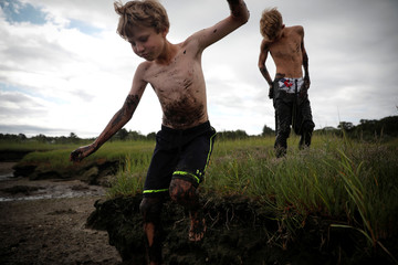 A boy leaps from the edge of a marsh while they enjoy playing in a mud bog at low tide in Barnstable Harbor on Cape Cod