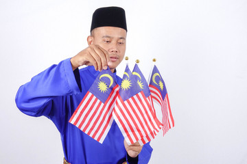 Asian young man with Malaysia flag for National Day celebration.