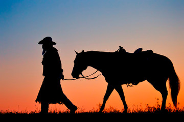 Silhouette of a Cowboy walking his Horse