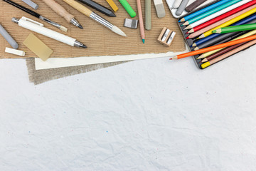 artist drawing tools: various colored pencils, chalks, paintbrushes on recycled paper background