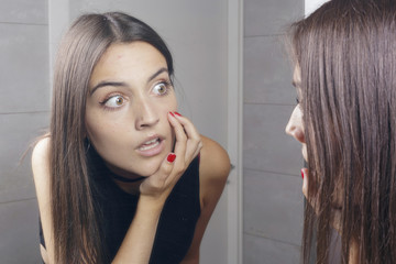 Surprised young woman finding acne on her face, standing before a mirror looking at her reflection. Indoors.