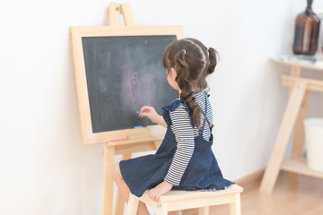 Happy asian girl kid draw cartoon with chalk on blackboard for learning at home. Photo for kid education and school study concept.