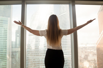 Confident businesswoman spreading hands standing at office window, enjoying big city, successful entrepreneur celebrating business success with arms open wide, feeling powerful inspired, rear view