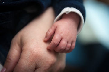 Mano rilassata di bimbo piccolo appoggiata sulla mano di un adulto