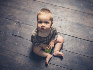 Little baby sitting on floorboards with apple
