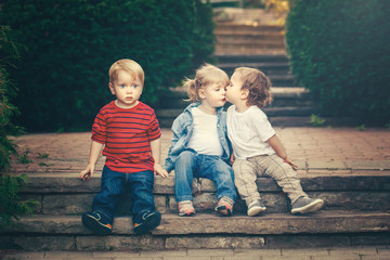 Group of three cute funny adorable white Caucasian children toddlers boys girl sitting together kissing each other. Love friendship childhood concept. Best friends forever. Toned with retro filters.