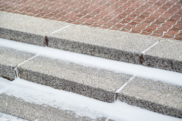 Close-up detail of snow and ice on the granite steps of a red brick sidewalk. Kyushu, Japan. Infrastructure and seasons concept.