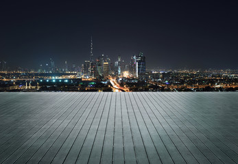 Wooden terrace with skyline of Dubai at night