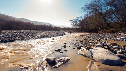Fast mountain river in bright sunlight, autumn landscape