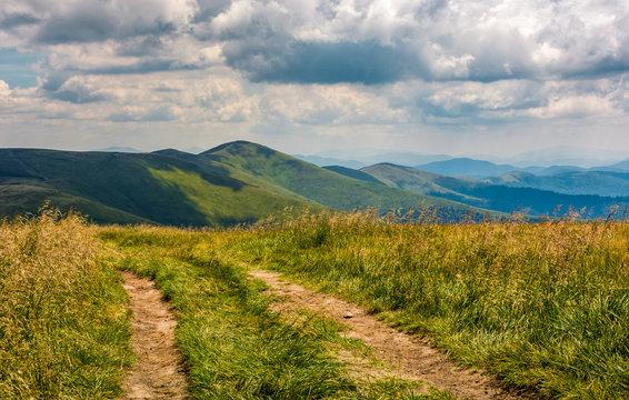dirt road through grassy meadow on the ridge
