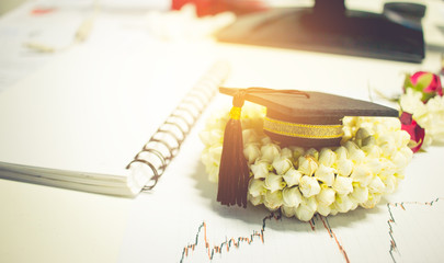 Concept of congratulate graduate study success, graduation black cap on Jasmine garland.,Education certificate of Abroad international university, diploma or certificate.