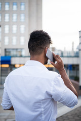 Young handsome Afro American man standing in front of huge modern business building, smiling and talking on mobile phone.