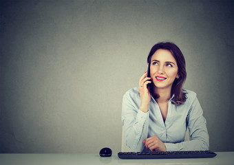 Young businesswoman sitting at office desk talking on mobile phone