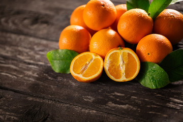 Sweet fresh oranges and half of orange on the wooden.