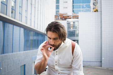 handsome guy with beard smocking cigarette on urban background with blue and gray glass
