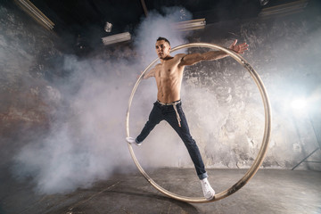 Strong circus performer spinning a cyr wheel Wall mural