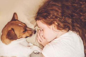 Sweet curly girl and dog is sleeping in night.
