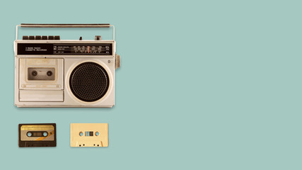 Radio cassette recorder and player with music tape cassette on color background. retro technology. flat lay, top view hero header. vintage color styles.