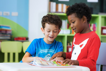 Student in international preschool reading a magazine book together