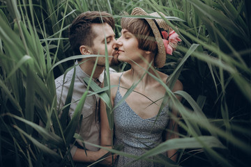 hipster couple posing at lake in cane in summer forest. stylish rustic bride and groom, girl in fashionable modern dress and straw hat with peony, embracing in windy high reed. rustic wedding concept