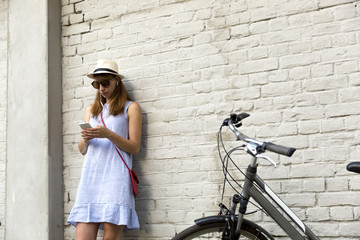 City life concept. Young woman standing next to the white brick wall listening to music in headphones