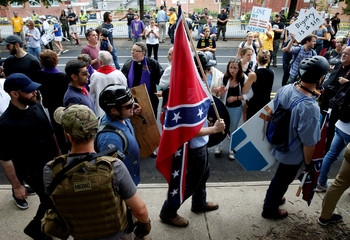 A white nationalist carries the Confederate flag as he walks past counter demonstrators in Charlottesville Virginia