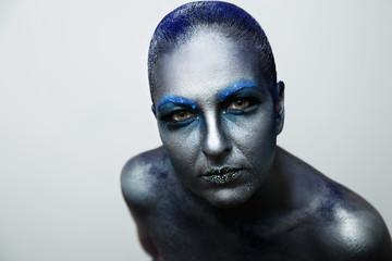 A stern gaze of a girl. Creative make-up in blue paint. blue hair