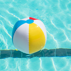 Bright multicolor beach ball floating in blue swimming pool, colorful float in a refreshing blue swimming pool with waves reflecting in the summer sun. Active vacation background. Lifesaver for kid.