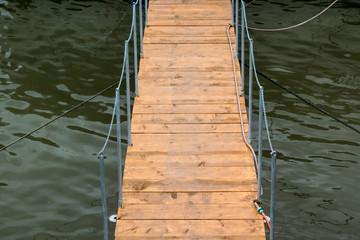 Wooden bridge from shore to pontoon alongside Danube river, Romania