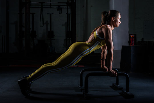 Parallettes woman parallel bars workout exercise at dark gym