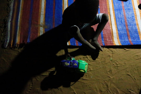 A child plays by a light bulb powered by a car battery in Al Fashir in North Darfur