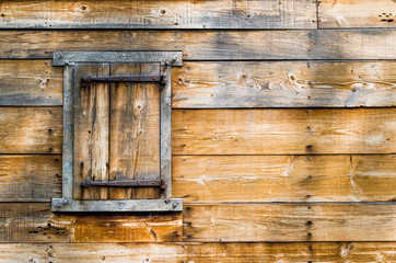 weathered wooden wall with shuttered window on left side