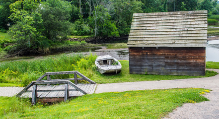 rustic colonial cabin with weathered rowboat and wooden footbridge