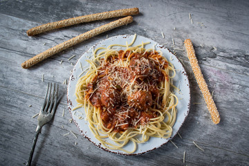 top view of spaghetti and meatballs plate with fork and breadsticks