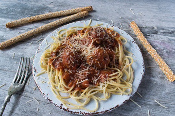 top view of spaghetti and meatballs with breadsticks