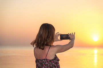 Girl is taking a sunset on a mobile phone