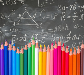 back to school pencils border on blackboard with math formulas