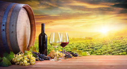 Poster Wijngaard Wine Glasses And Bottle With Barrel In Vineyard At Sunset