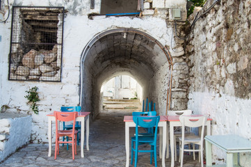 Courtyards of old town of Marmaris. Entrance to courtyard in form of an arch in  background of brick house next to table with colorful chairs in old town of Marmaris, Turkey
