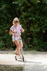 Little girl enjoys riding scooter
