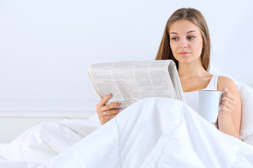 A pretty young woman reading the newspaper in bed and enjoying a cup of tea.