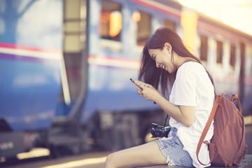 Traveler woman walking and waits train on railway platform.Vintage color