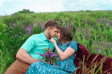 Loving couple sitting together in the middle of flowers on a meadow. Honeymoon